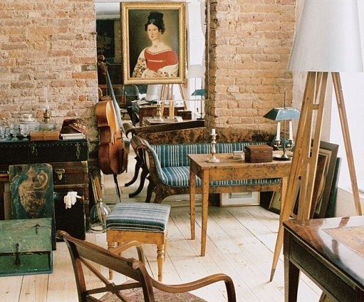 At the other end of the room, Dmitriev arranged a seating area made up of varied 18th-century furnishings and paintings. Exposed-brick walls and raw-toned wood floors add a sense of history to the room. For more light, the designer extended the lengths of the windows.
